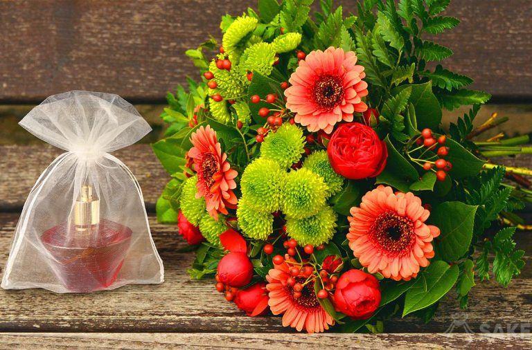 Woreczek z organzy z flakonem perfum i bukiet kwiatów